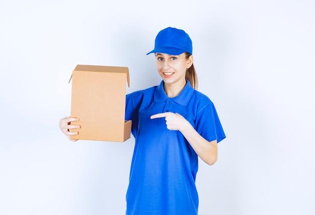 Dziewczyna w niebieskim mundurze trzyma otwarte pudełko kartonowe na wynos.