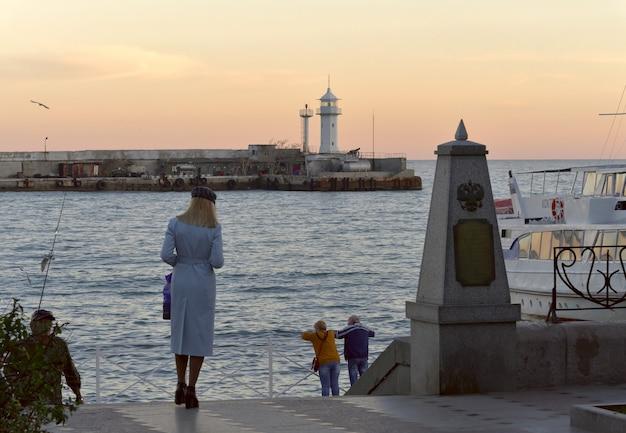 Dziewczyna w niebieskim płaszczu na głównym nabrzeżu jałtaty stolica południowego wybrzeża krymu