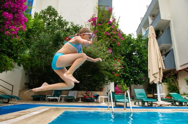 Dziewczyna w niebieskim stroju kąpielowym wskakuje do basenu. marmaris, turcja