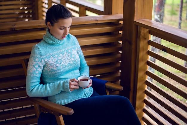 Dziewczyna w niebieskim swetrze siedzi na drewnianym krześle i popija herbatę z białego kubka na werandzie balkonu drugiego piętra w domu w sosnowym lesie.