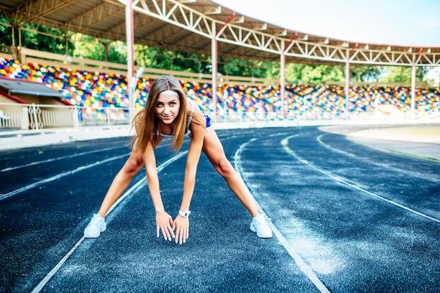 Dziewczyna w niebieskim szorty trening na stadionie