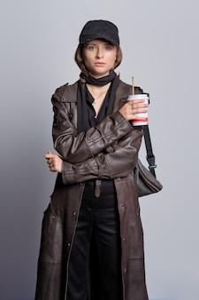 Dziewczyna w nieformalnym stroju - długi skórzany płaszcz, czarne dżinsy, bluzka, jedwabny szal i bazowa czapka