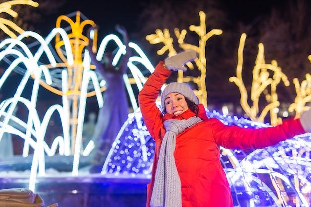 Dziewczyna w nocnym mieście śnieżynka boże narodzenie miasto świeci koncepcja świątecznych i zimowych wakacji
