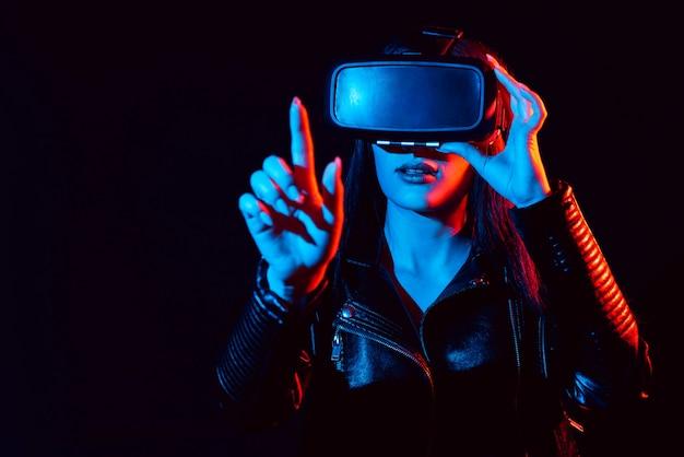 Dziewczyna w nowoczesnych okularach wirtualnej rzeczywistości na czarnym tle