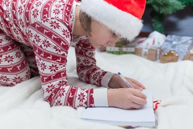 Dziewczyna w noworocznej piżamie i czapce świętego mikołaja pisze listę życzeń na świątecznym tle