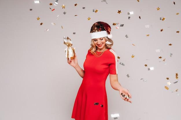 Dziewczyna w noworocznym kapeluszu z prezentem w dłoniach jest obsypana świątecznymi cekinami na szaro.
