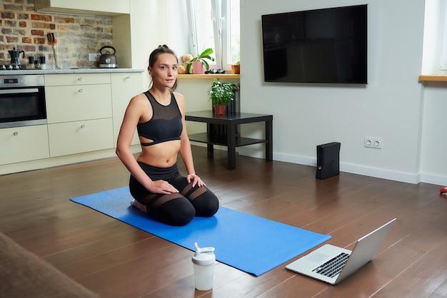 Dziewczyna w obcisłym garniturze do ćwiczeń robi trening jogi z wideo online na laptopie