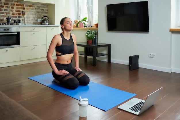 Dziewczyna w obcisłym kombinezonie do ćwiczeń relaksuje się po treningu jogi, oglądając wideo online na laptopie.