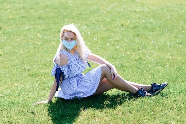 Dziewczyna w ochronnej masce medycznej na wiosnę wśród kwitnącego ogrodu. . wiosenna koncepcja alergii
