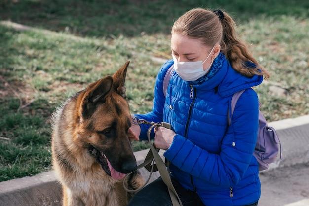 Dziewczyna w ochronnej masce medycznej wyprowadza psa na ulicę. wypoczynek ze zwierzęciem podczas kwarantanny. tryb izolacji i ochrony.