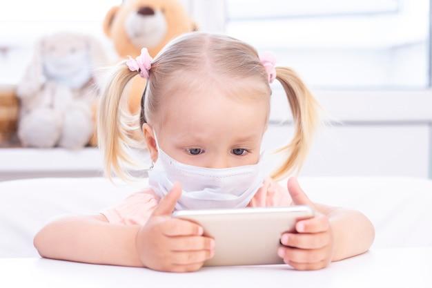Dziewczyna w ochronnej masce medycznej za pomocą telefonu komórkowego, siedząc w domu