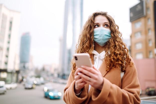 Dziewczyna w ochronnej sterylnej masce medycznej na twarzy z telefonem w mieście kwarantanny. kobieta szuka wiadomości za pomocą telefonu.