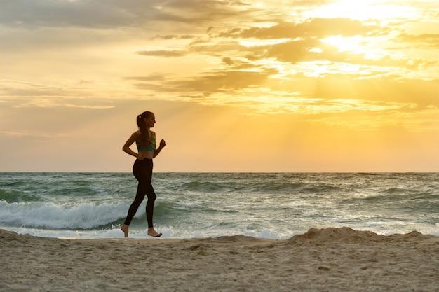 Dziewczyna w odzieży sportowej biegnącej wzdłuż linii surfowania. wcześnie rano