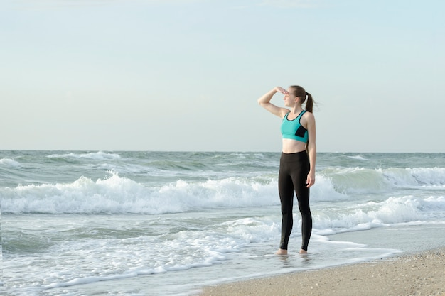 Dziewczyna w odzieży sportowej na plaży, patrząc na odległość. poranne słońce