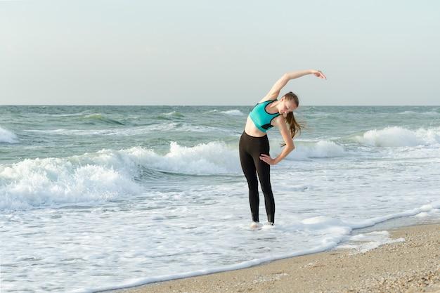 Dziewczyna w odzieży sportowej na plaży robi ćwiczenia.