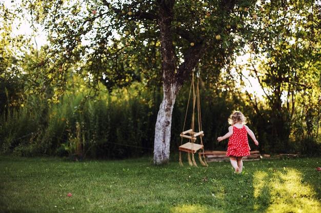 Dziewczyna w ogrodzie bawi się huśtawkami dziecko bawi się samotnie w ogrodzie