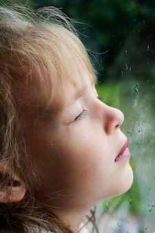 Dziewczyna w oknie z kroplami deszczu