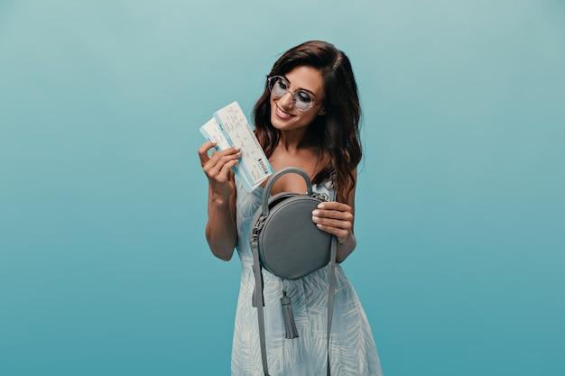 Dziewczyna w okrągłych okularach z uśmiechem wyciąga bilety z torby. brunetka z krótkimi włosami w niebieskiej sukience pozuje na na białym tle.