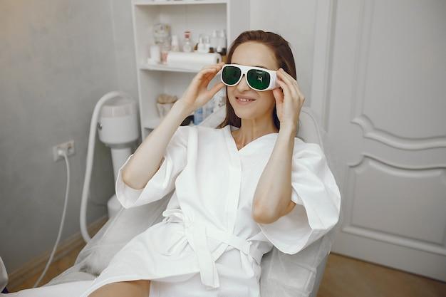 Dziewczyna w okularach bezpieczeństwa siedzi w studio kosmetologii
