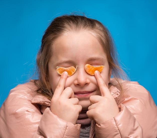 Dziewczyna w okularach mandarynki na niebieskim tle
