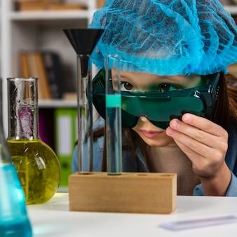 Dziewczyna w okularach ochronnych i siatce na włosy robi eksperymenty naukowe