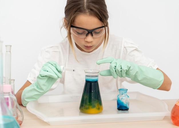 Dziewczyna w okularach ochronnych robi eksperymenty chemiczne w probówkach