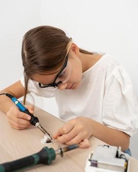 Dziewczyna w okularach ochronnych robi eksperymenty naukowe