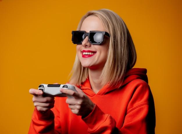 Dziewczyna w okularach przeciwsłonecznych bawi się joystickiem