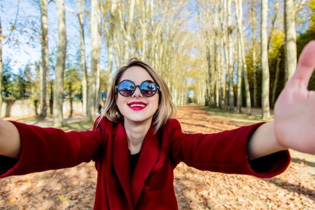 Dziewczyna w okularach przeciwsłonecznych i płaszcz w parku jesień