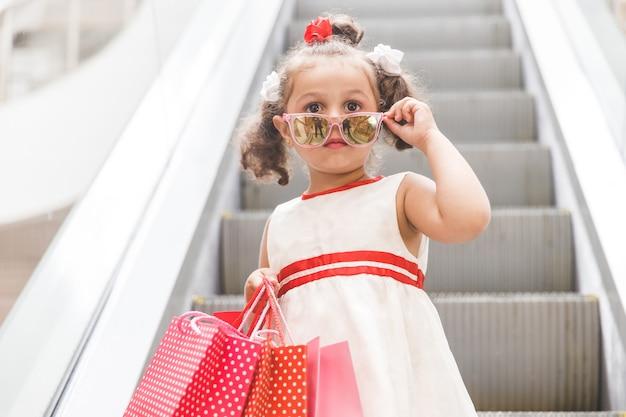 Dziewczyna w okularach przeciwsłonecznych na schodach ruchomych w centrum handlowym z kolorowymi torbami