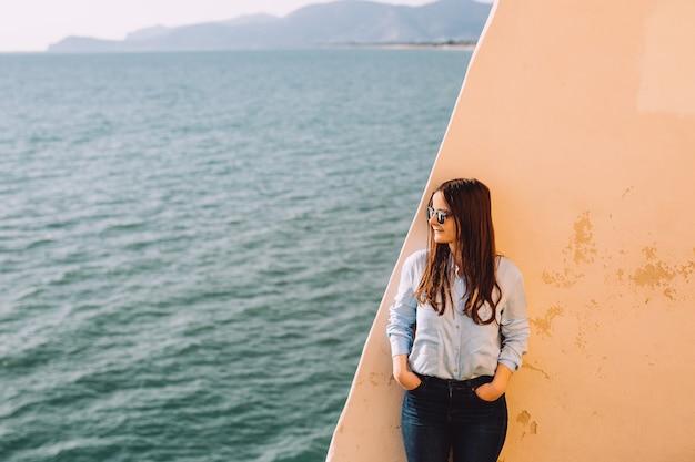 Dziewczyna w okularach przeciwsłonecznych opiera się o żółtą ścianę w pobliżu morza.