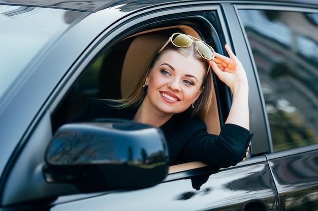 Dziewczyna w okularach przeciwsłonecznych prowadzi samochód i patrzy z okna