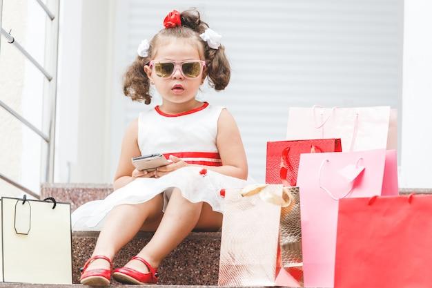 Dziewczyna w okularach przeciwsłonecznych siedzi na schodach w centrum handlowym z kolorowymi torbami
