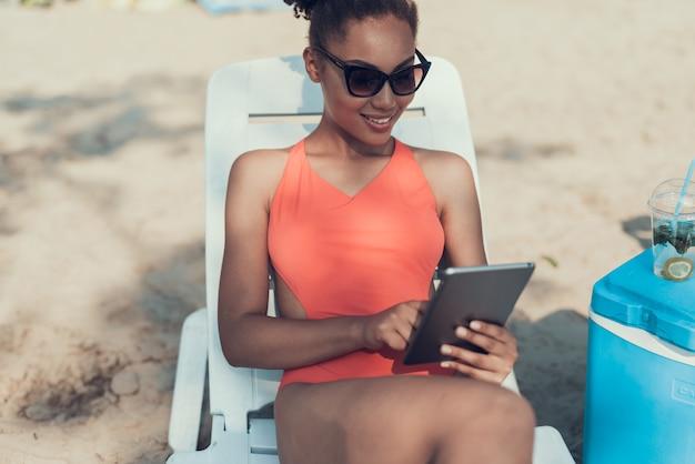 Dziewczyna w okularach przeciwsłonecznych używa tabletu pc. słoneczny dzień.