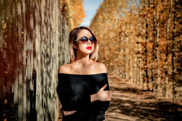 Dziewczyna w okularach przeciwsłonecznych w jesień sezonu parku