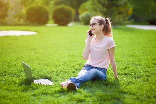 Dziewczyna w okularach rozmawia przez telefon, siedząc na trawie