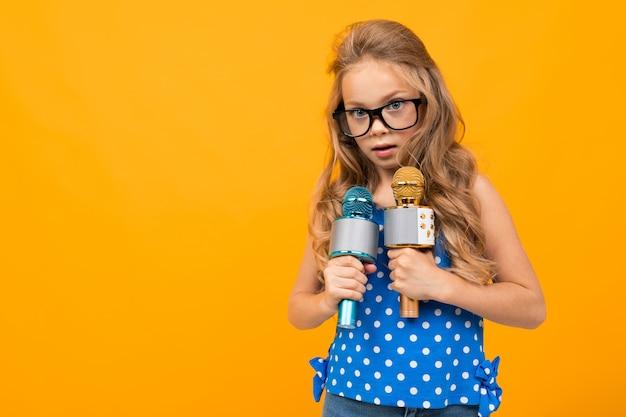 Dziewczyna w okularach trzyma dwa mikrofony na pomarańczowej ścianie