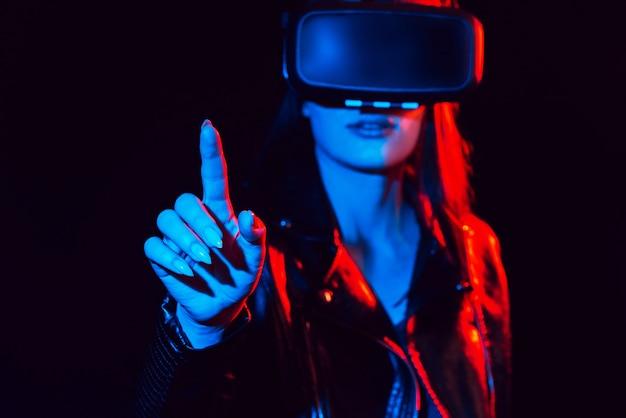 Dziewczyna w okularach wirtualnej rzeczywistości dotyka palcem ekranu projekcyjnego