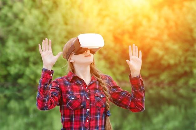 Dziewczyna w okularach wirtualnej rzeczywistości trzyma ręce w górę, na tle