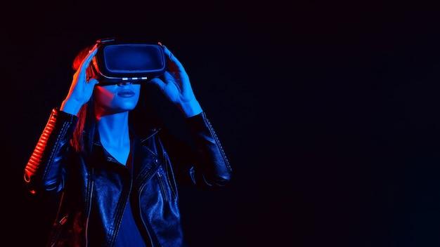 Dziewczyna w okularach wirtualnej rzeczywistości z czerwonymi i niebieskimi światłami na czarnym tle