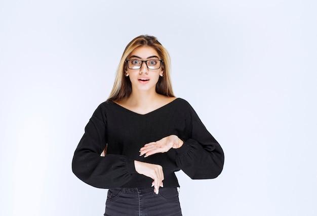 Dziewczyna w okularach, wskazując na zegarek.