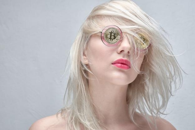 Dziewczyna w okularach z bitcoinami na białym tle