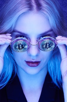 Dziewczyna w okularach z bitcoinami