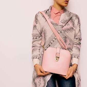 Dziewczyna w ozdoby sweter i akcesoria mody. torba i stylowe niebieskie dżinsy