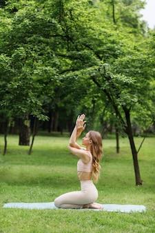 Dziewczyna w parku latem trenuje jogę