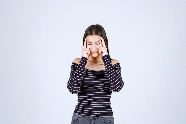 Dziewczyna w pasiastej koszuli myślenia i analizowanie.