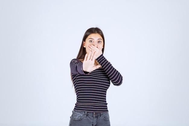 Dziewczyna w pasiastej koszuli prosi o ciszę.