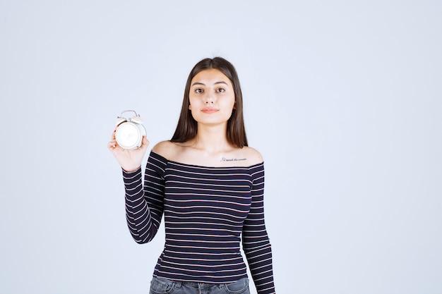 Dziewczyna w pasiastej koszuli trzyma budzik i promuje go jako nowy produkt.