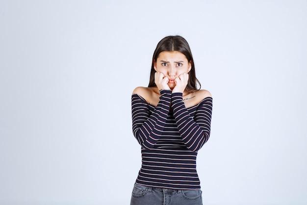 Dziewczyna w pasiastej koszuli wygląda na przerażoną i przestraszoną.