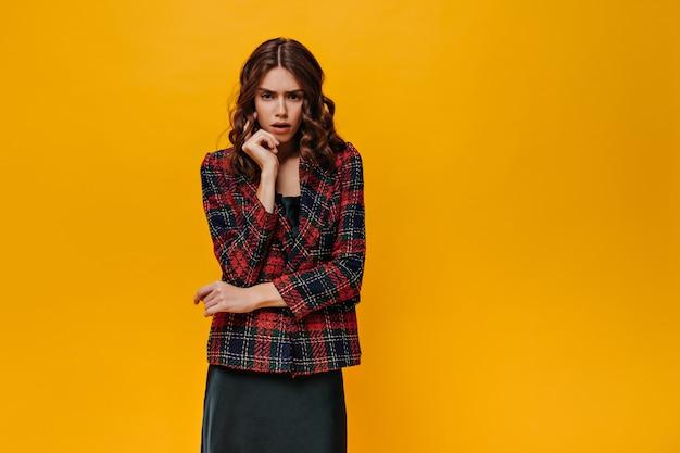 Dziewczyna w pasiastej kurtce pozuje na izolowanej ścianie